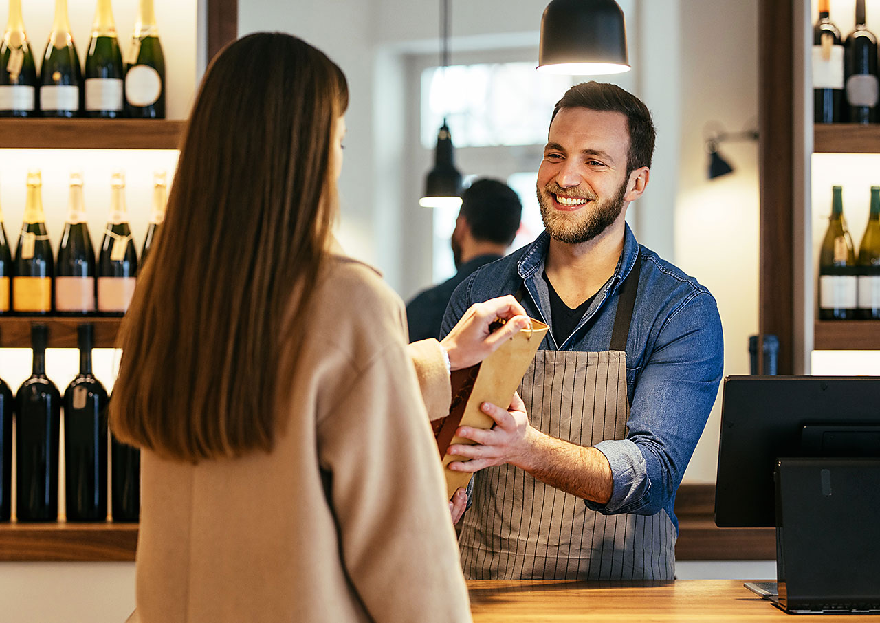 Woman buying wine from man in wineshop