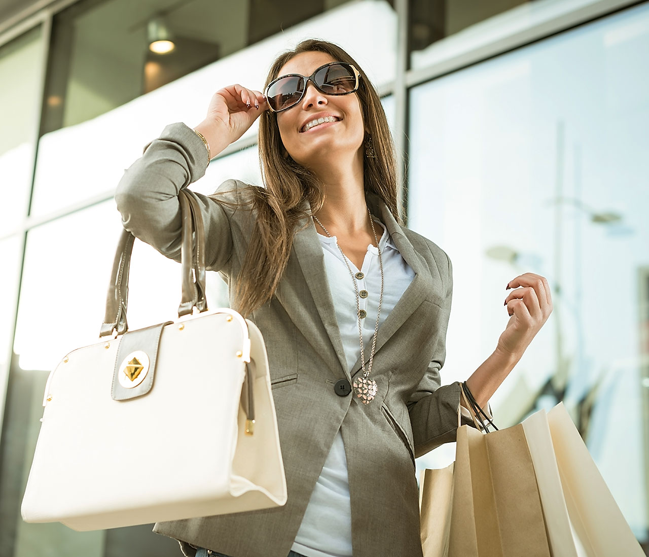 Woman with sunglasses carrying shopping bags